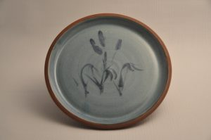 Plate with no rim, glazed only on top surface in teal with cobalt rushes painted under the glaze