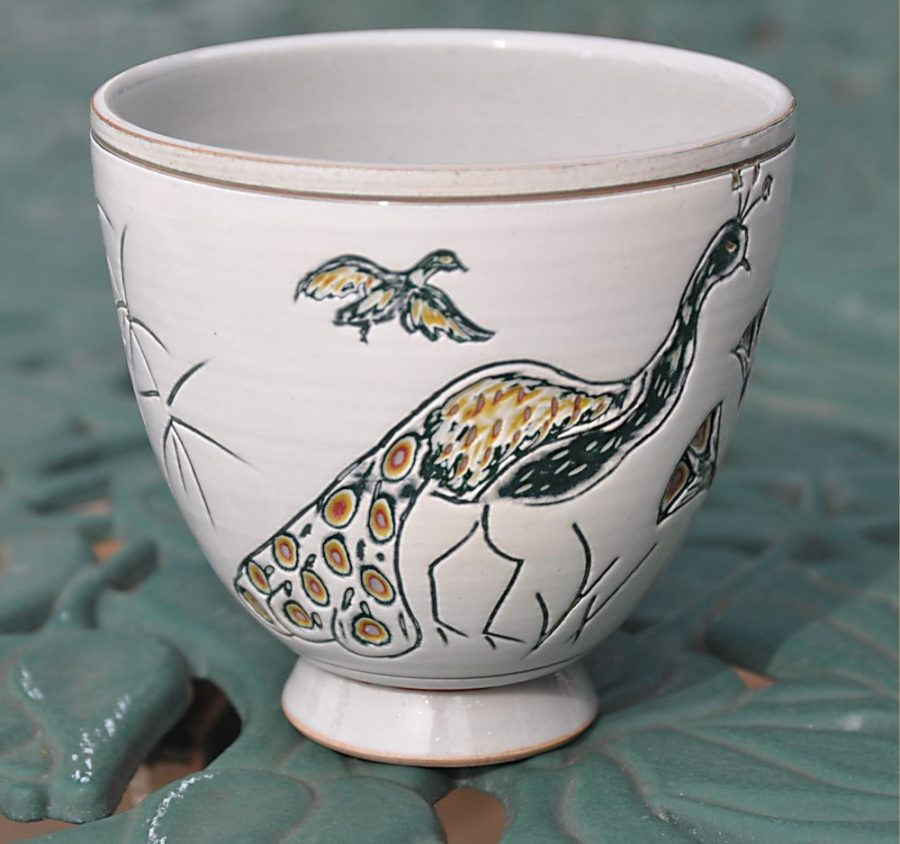 Handeless cup painted with 5 different colours of slips and carved through