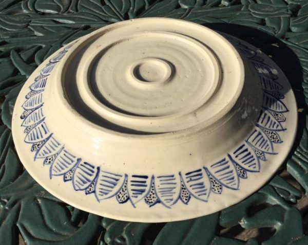 Underside of Andalusian platter painted under rim with blue and black leaf like shapes