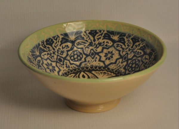 Sgraffito tall footed bowl - in profile - interior is slipped in black, blues and green and carved through