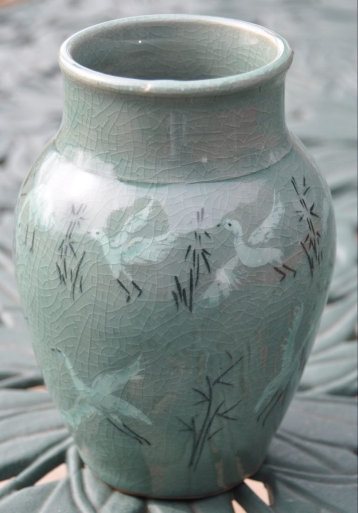 Celedon vase decorated with incised cranes and grasses, filled with white and black slips