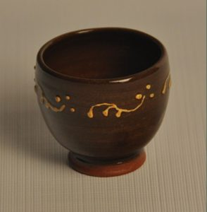 Shot glass or egg cup in red clay, slip trailed vines in white glazed in an amber gold
