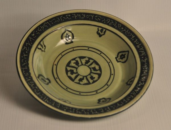 Reproduction Persian plate with black slip decoration painted and carved through, glazed in celedon green