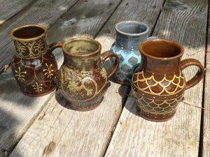 4 red clay mugs decorated with slip and carved through in a variety of glazes