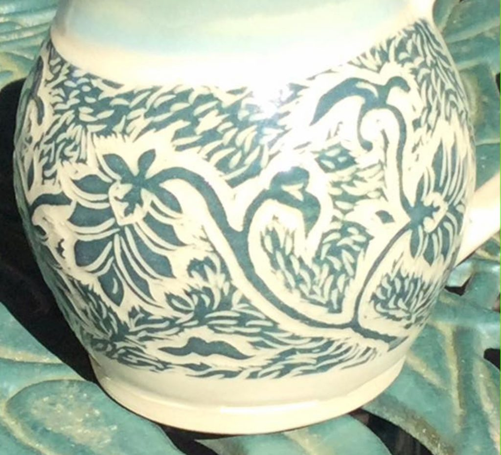 Carved detail of leaves and flowers on a mug in green on white clay