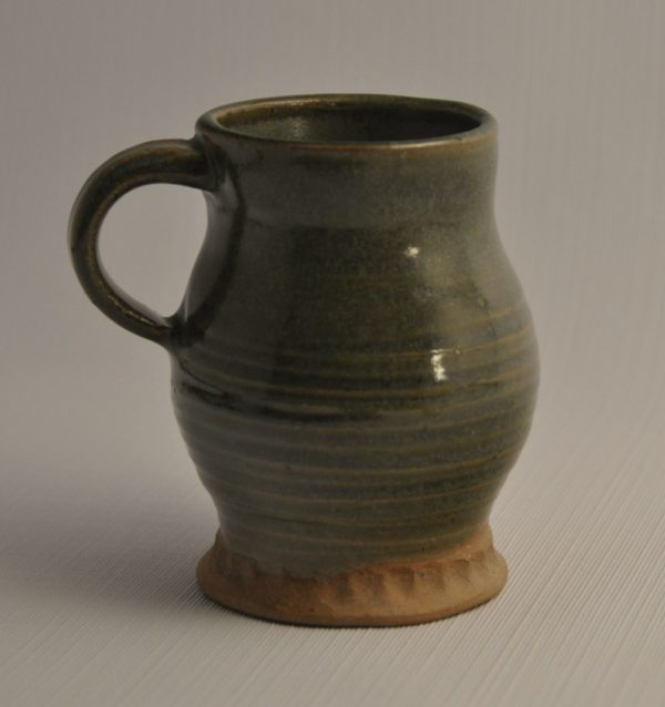 Small mug with pinched base, glazed overall in green with small loop handle