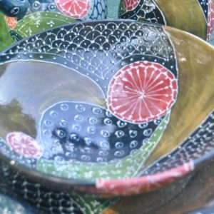 Shallow bowl slip trailed and painted with underglazes in curving lines reminiscent of Persian fabric designs